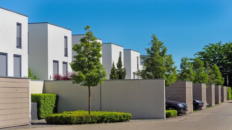Weiße Neubauten in Reihenhaussiedlung mit Bäumen und Mauern im Vorgarten