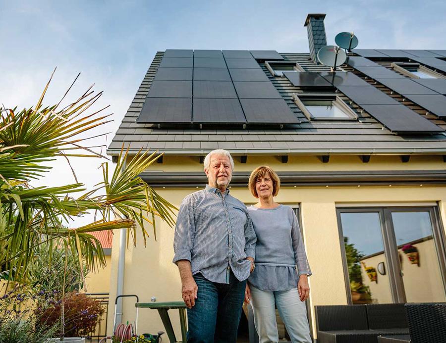 Ehepaar vor Eigenheim mit Solaranlage auf dem Dach