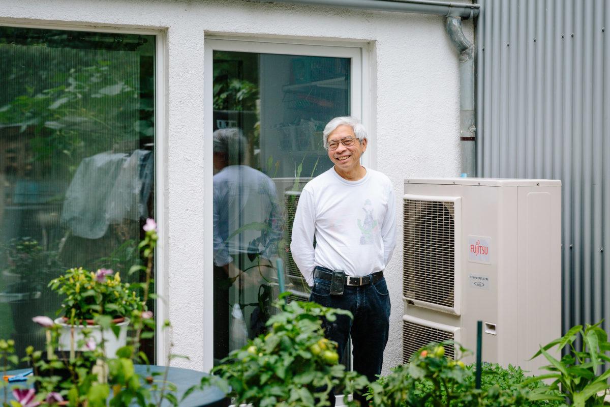 Mann auf der Terrasse seines Hauses mit Wärmepumpe