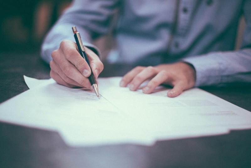Mann in Hemd bei Vertragsunterschrift