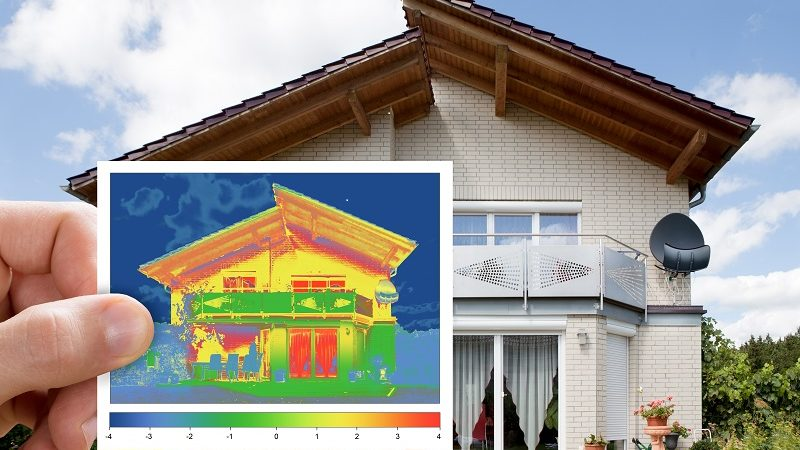 Person Hand Holding Infrared Thermovision Image Showing Lack Of Thermal Insulation Outside The House