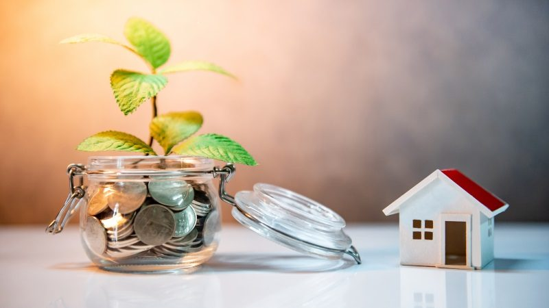 Property or real estate investment. Home mortgage loan rate. Saving money for future concept. Reflection of green plant growing out of coins in glass jar and house model on the table