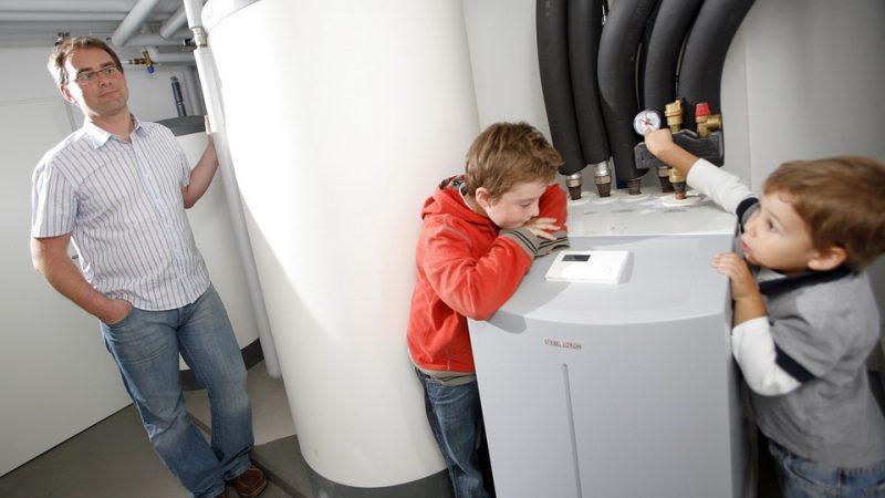 Vater und zwei Kinder im Heizungskeller mit Kombispeicher und Inneneinheit der Wärmepumpe